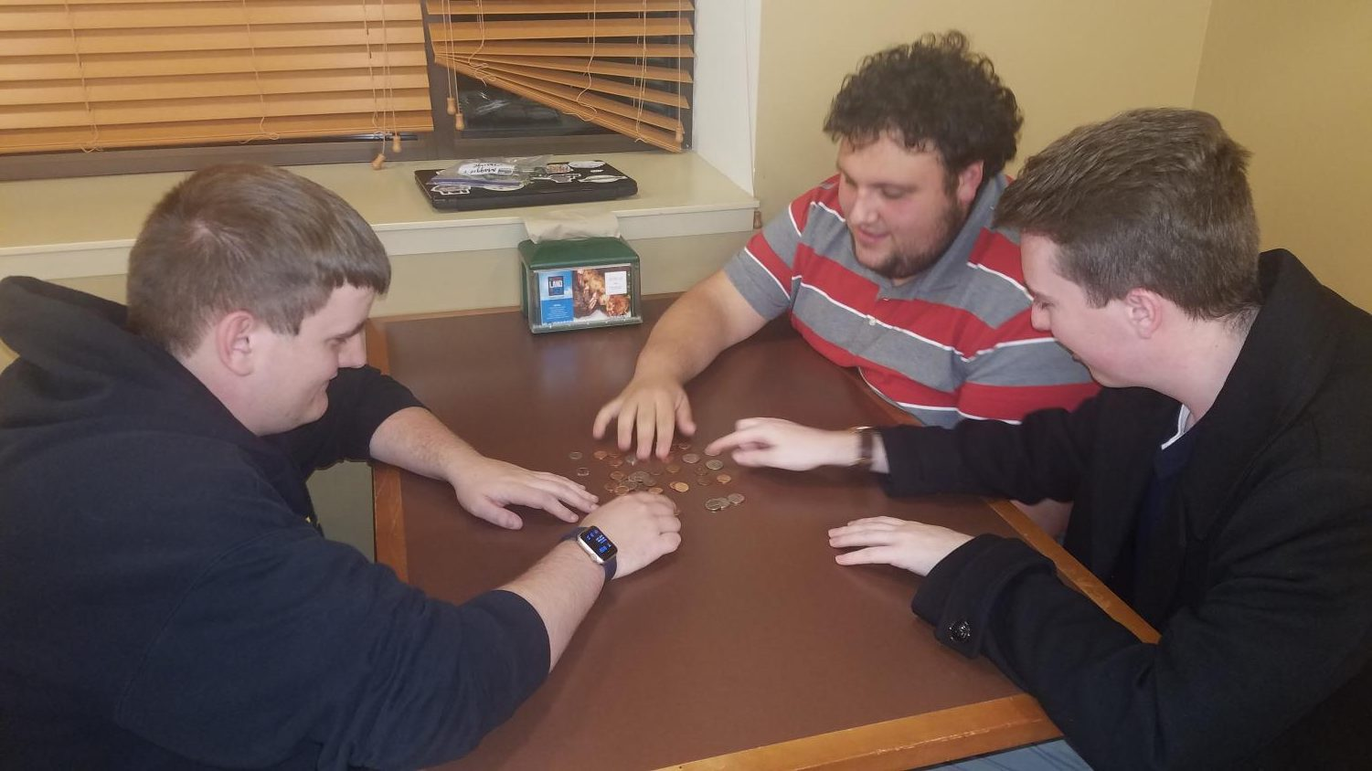 Michael Songer, a junior JUHAN fellow, helps sort coins for the Penny Wars competition with junior Daniel Mulvihill and senior Matthew Pollock in the Le Moyne Den on Oct 17.