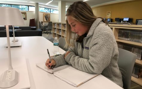 Sarah Buck, first-year Biology student and Promise NY scholarship recipient, does homework in the library on Thursday, Oct. 18.
