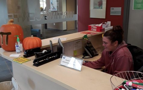 Student Sidney Hall works at the Writing Center front desk.